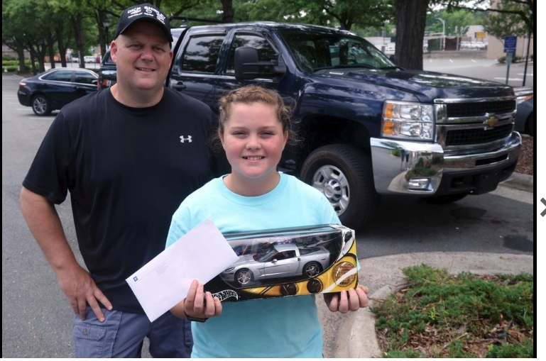 Brianna White, 10, a 4th grade student at E.M. Holt Elementary displays her letter and gift from the CEO of Chevrolet with her father, Chris White and his 2009 Chevrolet Silverado 2500HD pickup truck.