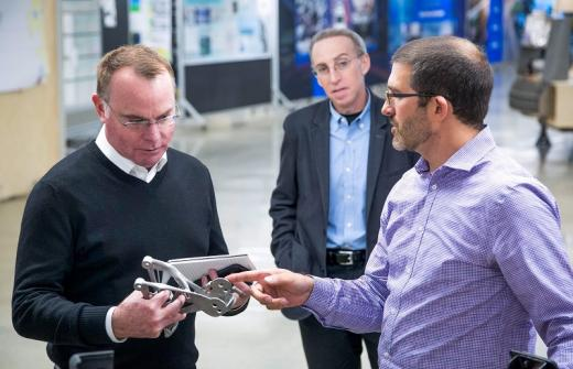 GM Director of Additive Manufacturing and Generative Design Kevin Quinn (right) shows Amend 3-D printed, proof-of-concept seat bracket.